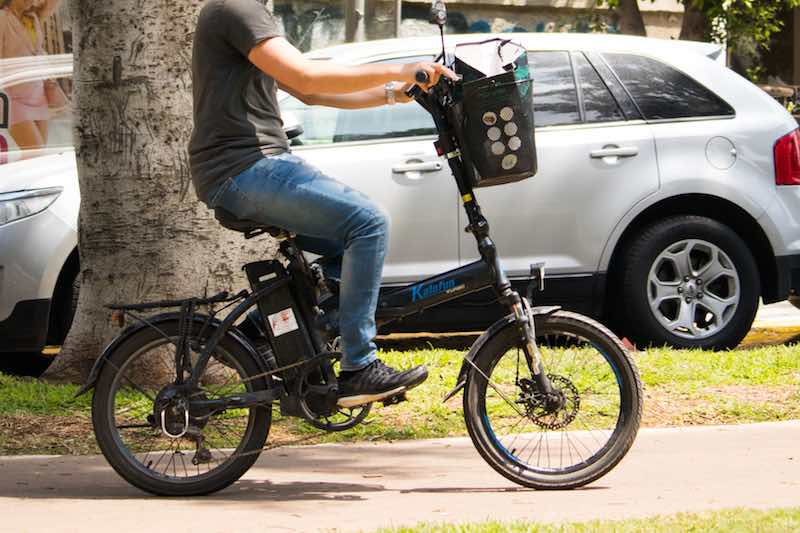 Man riding folding electric bicycle in the city